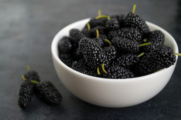 The mulberry in a white bowl on the black table.