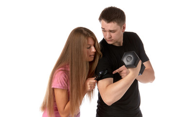 The beautiful girl considers a biceps of the young man by means of a magnifier.
