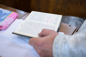 The priest holds the Bible at the altar, church utensil, the Bible on the table, ceremony of water baptism christening
