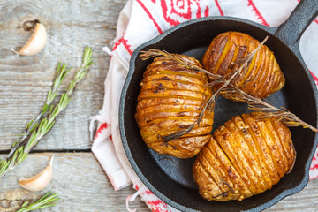 Baked potatoes with rosemary in a cast-iron frying pan.