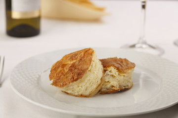 Cheese puff pastry arranged on a plate, Wine bottle and wineglass in background, Traditional dish in elegant setting, Selective focus with soft light