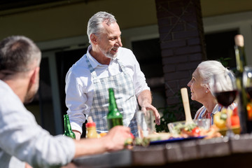 happy family talking during lunch on patio at daytime