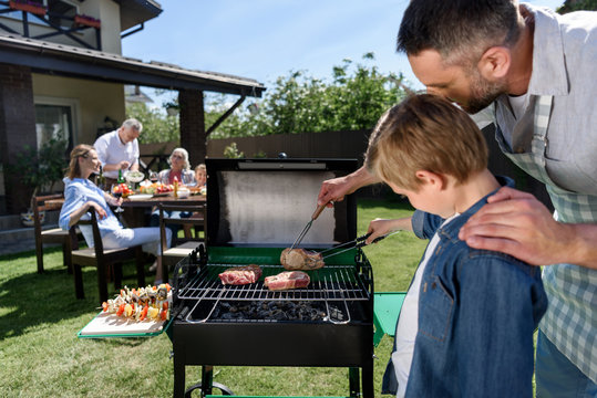 Close-up view of father and son grilling meat while family sitting at table outdoors