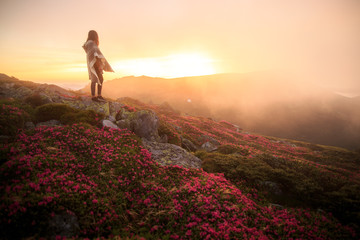 young woman hiking at mountain peak above clouds and fog. Hiker girl wrapping in warm poncho outdoor. Young girl over the clouds. Wonderful landscape with cloud inversion. Flowers in the mountains