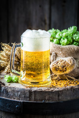Pint of beer with foam, hops and wheat on barrel