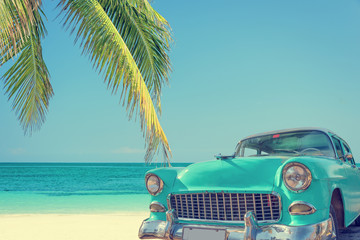 Classic car on a tropical beach with palm tree, vintage process
