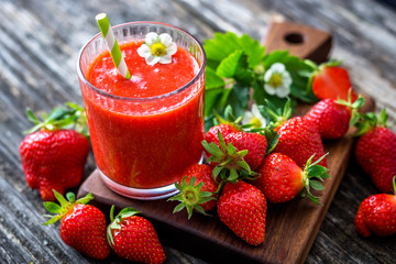 Strawberry smoothie and strawberries on wooden background