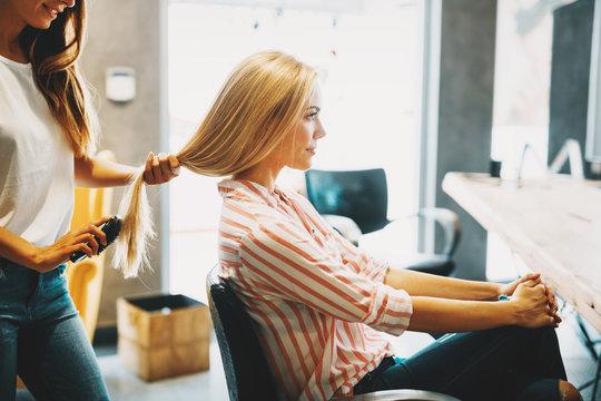 Portrait of beautiful young woman getting haircut