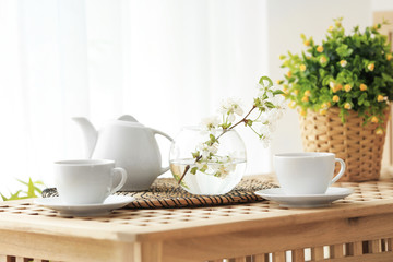 Tea set and vase with beautiful flowers on wooden table