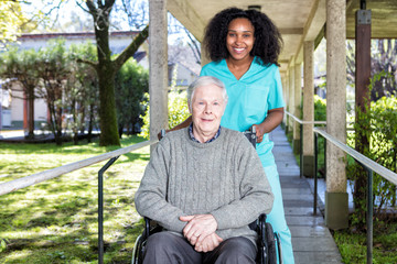 African nurse helping man on the wheelchair