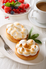 Tart with lemon curd, merengue and coffee with milk close-up. vertical