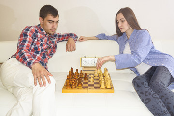 Relaxed young couple playing chess at home lying on sofa. won - Friendship.
