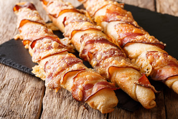 Freshly baked bread sticks with bacon and cheese close-up. horizontal