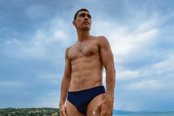 Muscular man standing on the beach in a speedo. The concept of freedom, power, sport, healthy lifestyle.