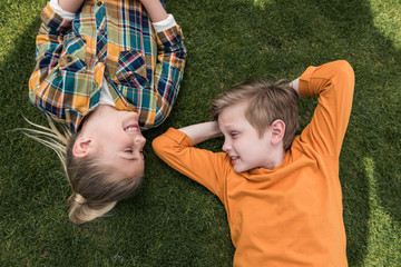 top view of little boy and girl looking at each other while lying on green lawn