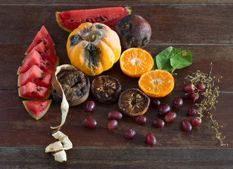 Pile of withered and rotten fruits on old old brown wooden floor / Still Life image and  Selective focus.