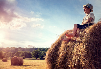 Boy sitting on a haystack watching the sunset