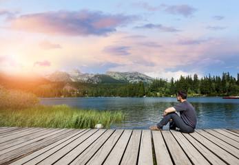 Man sitting on the bank of alpine mountain lake at sunset