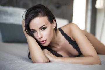 Sexy brunette woman in underwear lying on bed