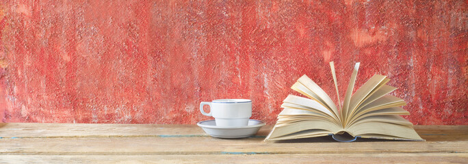 open book on red grungy background and cup of coffee, good copy space