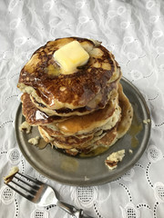tall stack of hotcakes with butter and syrup on white linen
