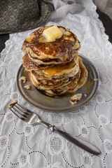 tall stack of pancakes with butter and syrup on white linen tablecloth