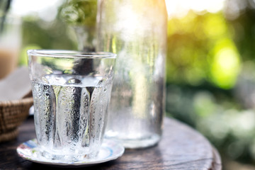 A glass of cold water and bottle on wooden table with blur nature background