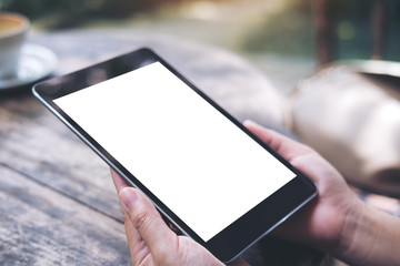 Mockup image of woman's hands holding black tablet pc with white blank screen with vintage wooden table background