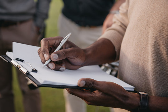 cropped view of african american man writing something on paper in clipboard