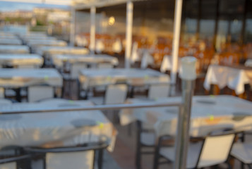 Blurred dining table restaurant with beautiful ocean view at twilight scene.