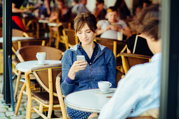 people, communication and dating concept - couple with smartphones drinking tea or coffee in strret table of cafe or restaurant