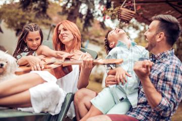 Family having fun,playing the guitar
