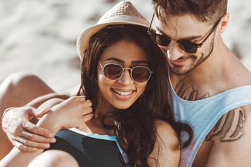 Happy young couple in sunglasses sitting and embracing on beach