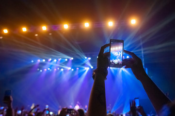 People in the crowd at a concert make video recordings and pics on a smartphone of published in social networks