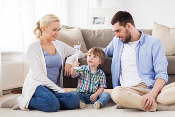 happy family playing with toy wind turbine