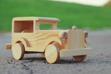 old wooden toy car on the road outdoors in the park
