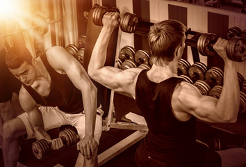 Men with dumbbells at gym. Group of friends training muscles at sport room. Back view. Color sepia tone on shiny sunlight background.