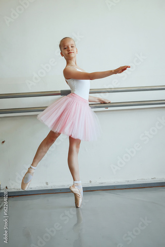 3f96d2931 Cute little ballerina in pink ballet costume and pointe shoes is ...