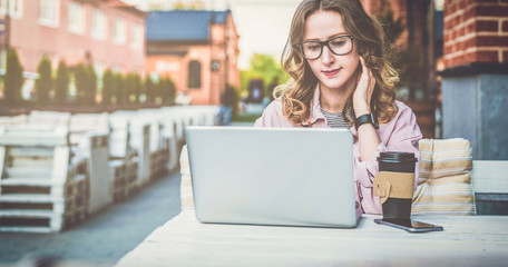 Front view.Young businesswoman with glasses is sitting at table in street cafe and uses laptop.