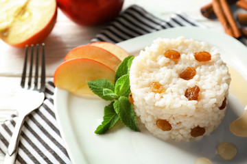 Plate with sweet rice and apple slices on on table, closeup