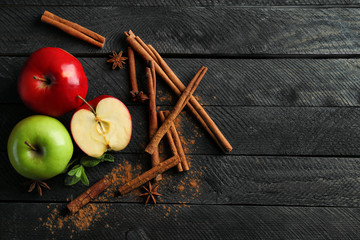 Composition with fresh apples and cinnamon on dark wooden table