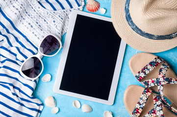Summer women's accessories: sunglasses, hat, sandals, shirt and tablet on blue  background. Vocations, travel and freelance work concept. Top view