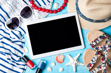 Summer women's accessories: sunglasses, hat, jewelry, sandals, shirt and tablet on blue background. Vocations, travel and freelance work concept. Top view