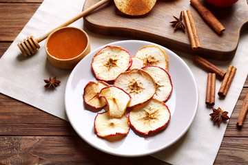Composition with tasty apple chips and cinnamon on wooden table