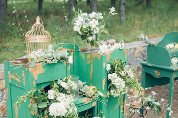 Beautifully decorated photo zona for wedding. Green chest of drawers decorated with white flowers