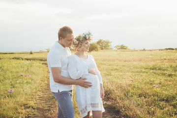 beautiful pregnant girl and her husband in the nature