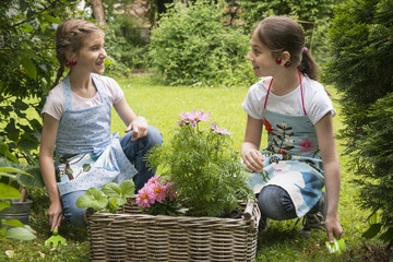 Two girls with flowers in a basket planting together