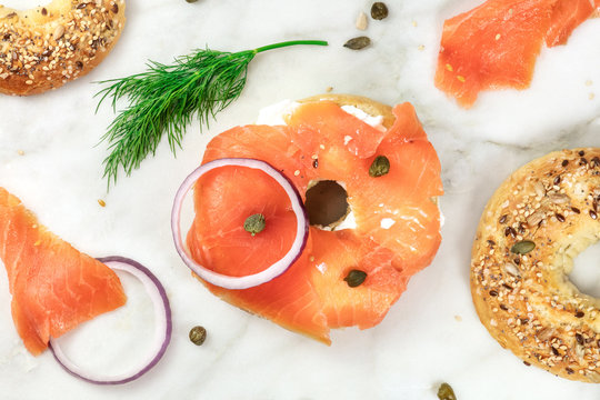 Making lox bagels, overhead photo on white marble background