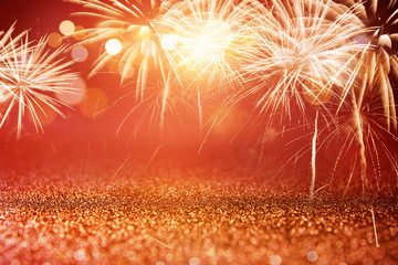 Fototapete - Holiday Red and Gold Fireworks and bokeh in New Year eve and copy space. Abstract background celebration.