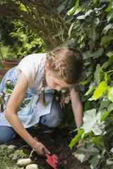 Girl gardening, working carefully with trowel
